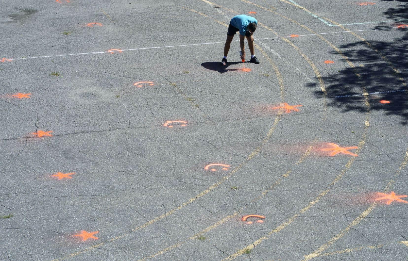 Un enseignant peignait des marqueurs dans la cour d'une école primaire pour faciliter la distanciation physique des élèves, en août dernier.