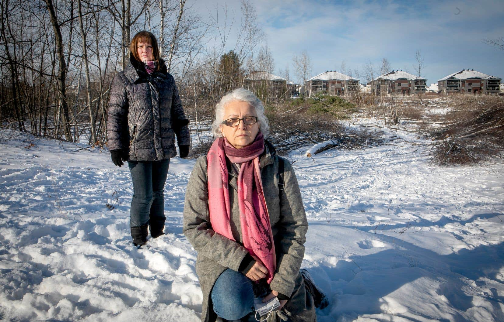 Sylvie Clermont (à l'avant) et Guylaine Thibodeau, devant le boisé de Sainte-Marthe-sur-le-Lac au cœur du litige