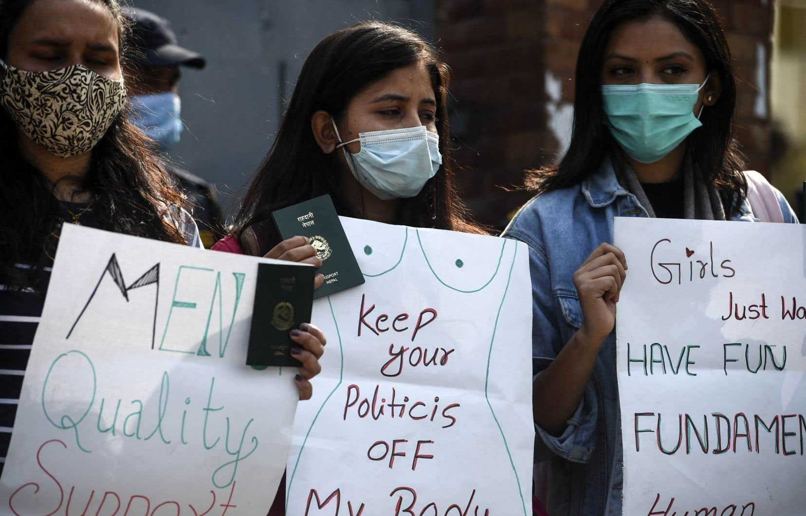Des militantes des droits des femmes tiennent des pancartes devant le bureau du ministère de l'Immigration du Népal lors d'une manifestation à Katmandou le 11 février 2021.