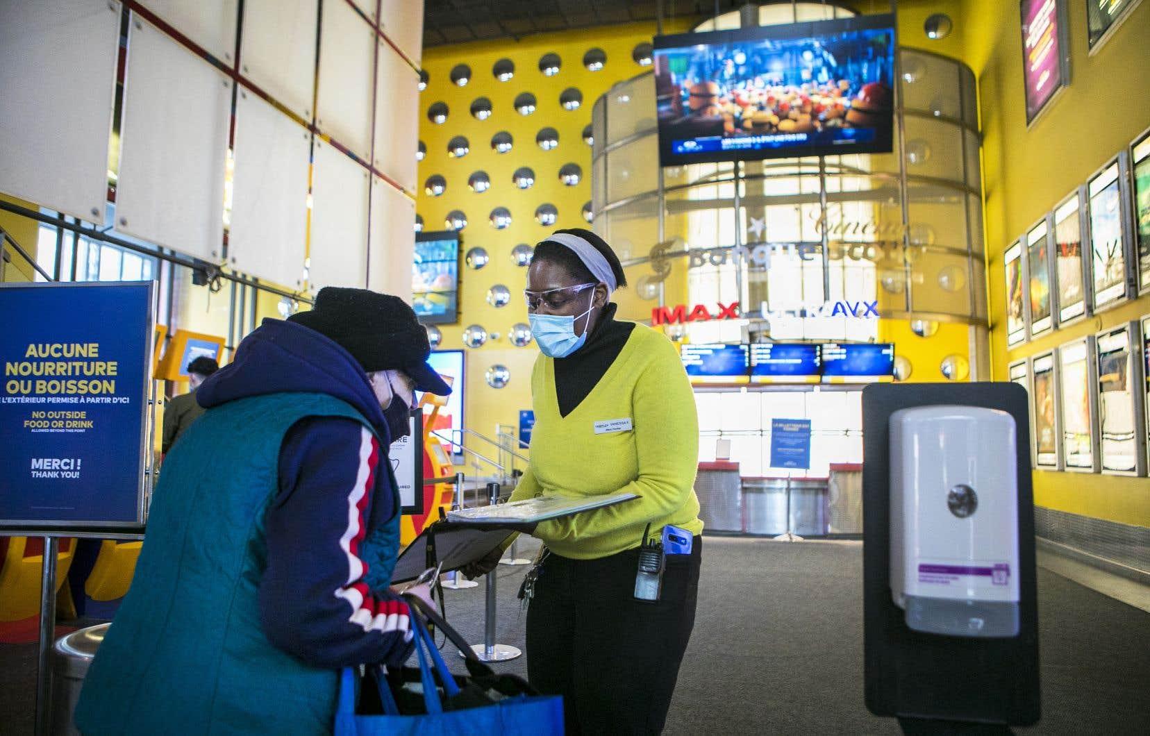 Une employée du Cineplex Banque Scotia, au centre-ville de Montréal, répétait les consignes sanitaires aux visiteurs qui y entraient, vendredi.