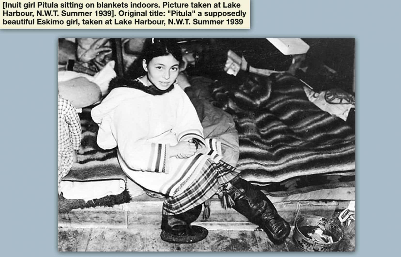 La photo et sa légende proviennent de Bibliothèque et Archives Canada, sous la référence Mikan 5034383. La photo prise en 1939 à Lake Harbour dans les Territoires du Nord-Ouest était identifiée par ce titre (en anglais) : « Pitula, une fille esquimo prétendument jolie ». Un ajout annonce maintenant : « La jeune Inuit Pitula assise à l'intérieur sur des couvertures. »