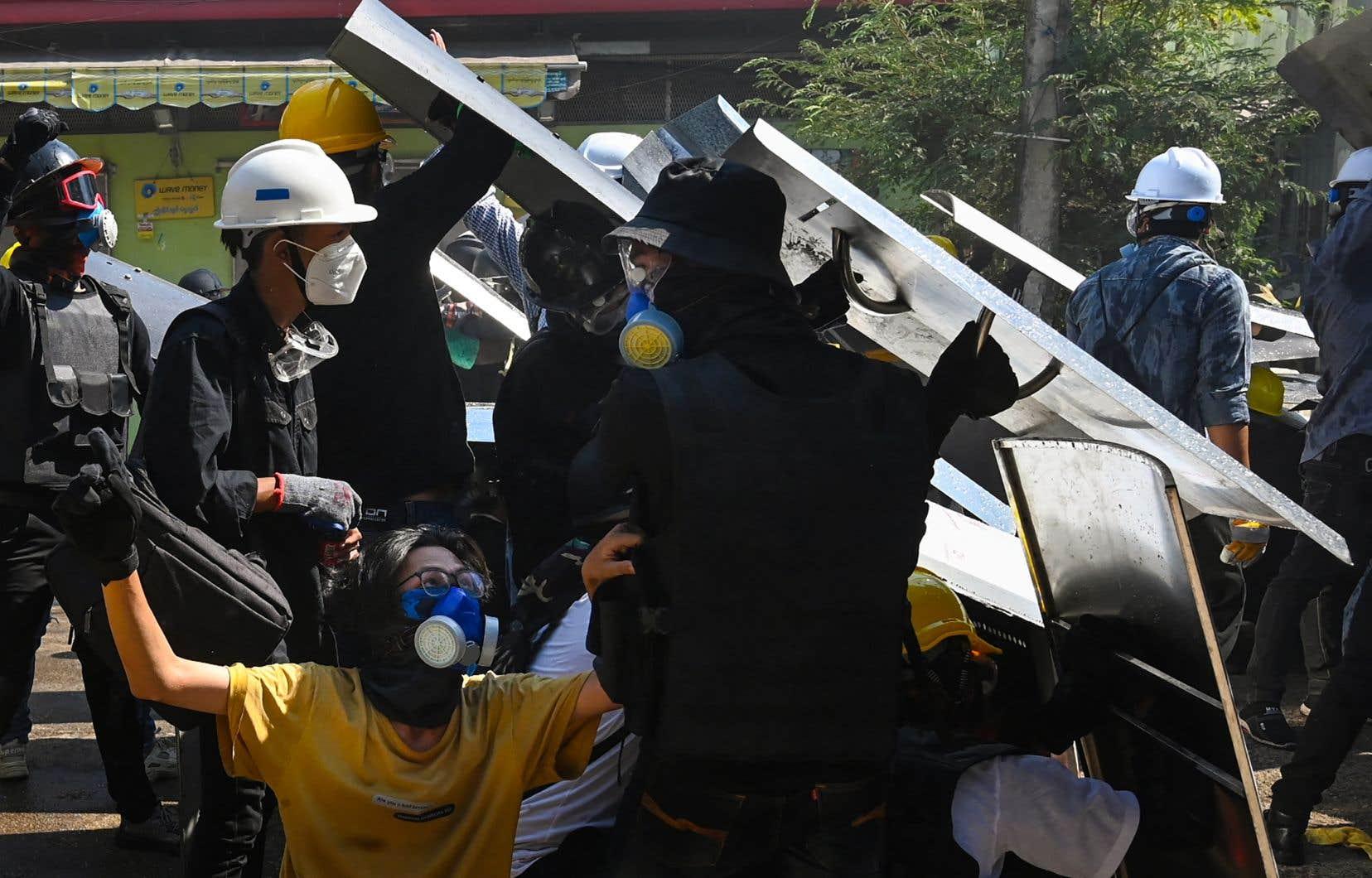 Comme depuis plusieurs semaines, des Myanmarais sont descendus dans les rues de Rangoun, maintenant équipés pour certains de boucliers et de masques à gaz.