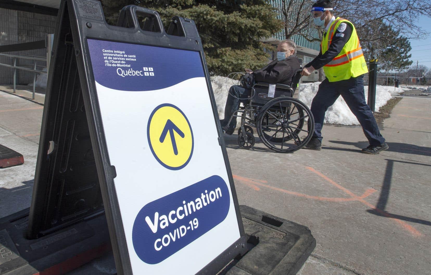 Un aîné reçoit de l'aide pour se faire vacciner dans une clinique de vaccination COVID-19, le lundi 8 mars 2021 à Montréal.