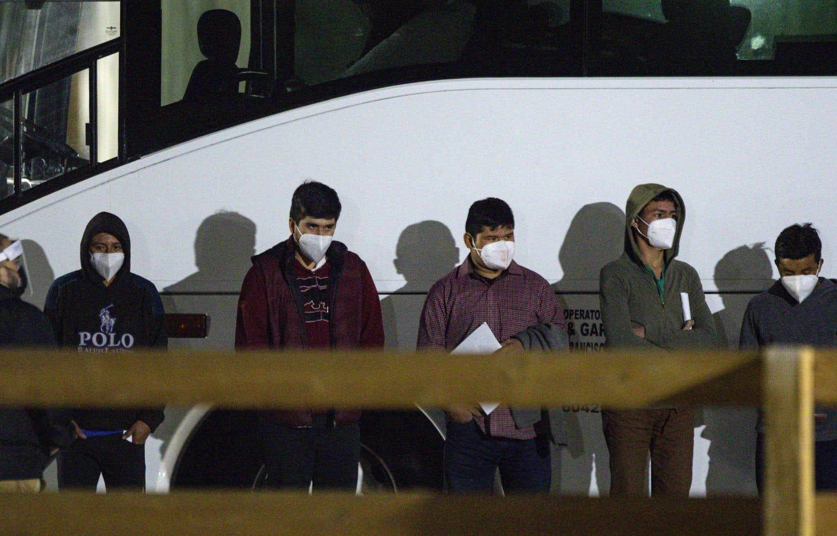 Des adolescents attendaient  dimanche soir de pouvoir  accéder  à un site  d'hébergement temporaire  au Texas, après avoir franchi  la frontière  séparant  les États-Unis  du Mexique.