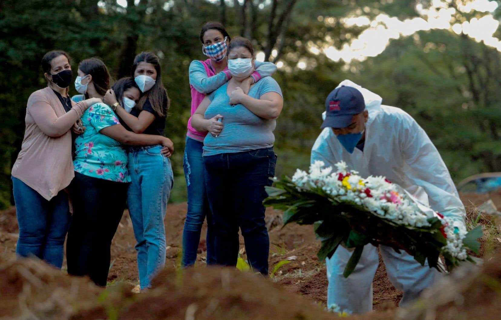 Dans la dernière semaine, plus de 19 000 personnes ont péri de la COVID-19 au Brésil, selon les plus récentes données de l'université Johns Hopkins, qui enregistre également une nouvelle flambée de contaminations dans ce pays, avec plus de 87 000 nouveaux cas détectés en 24 heures à peine. Sur la photo, les proches d'une victime de la COVID-19 assistent à son enterrement dans un cimetière de São Paulo.