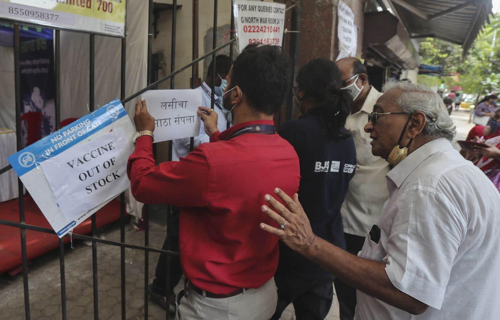 Un travailleur de la santé affiche un avis sur la pénurie de vaccins contre le coronavirus (COVID-19) devant un centre de vaccination à Mumbai, en Inde, le jeudi 8 avril 2021.