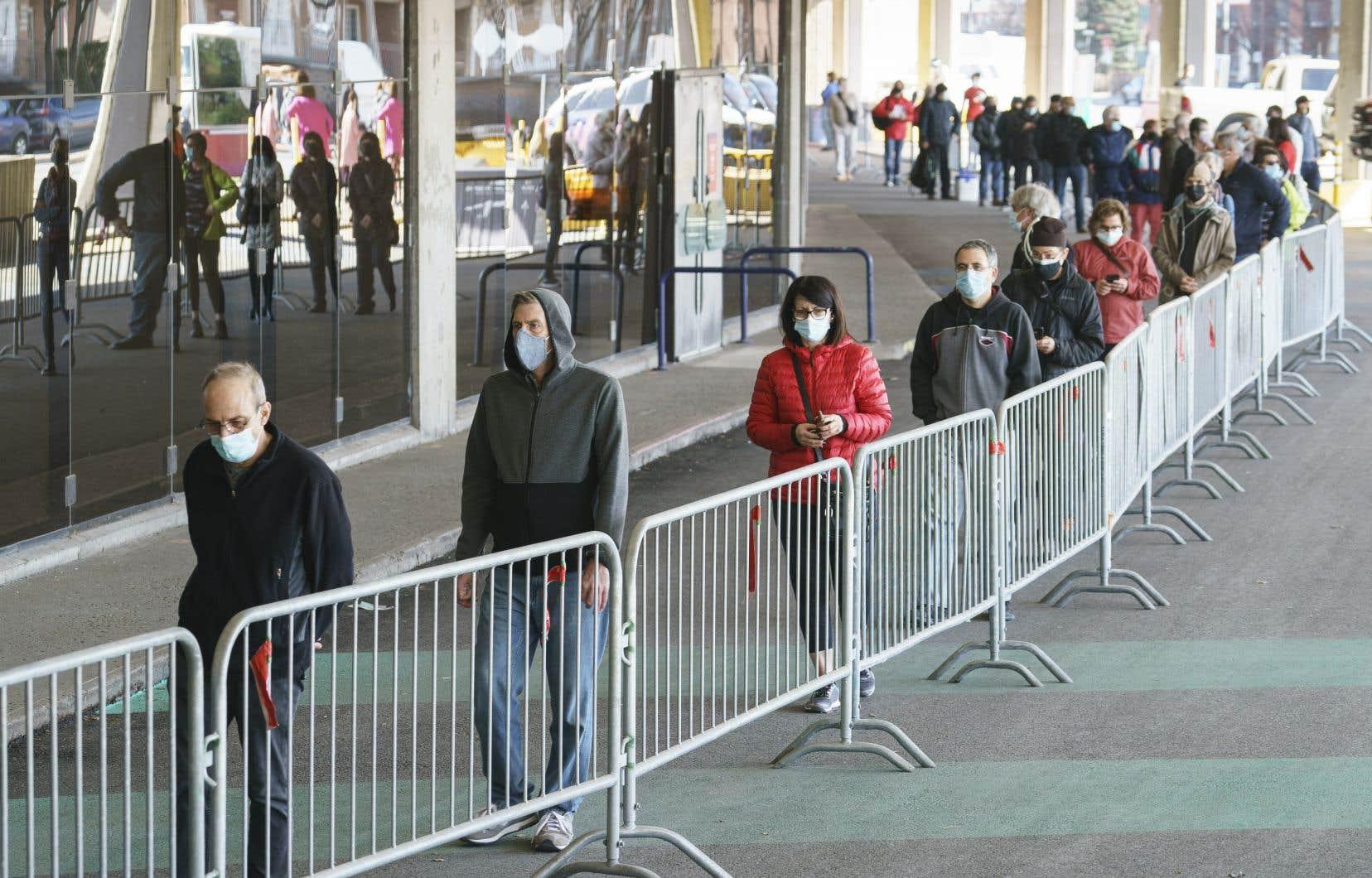 Des personnes font la file au Stade olympique de Montréal pour aller se faire vacciner, sans rendez-vous, contre la COVID-19.