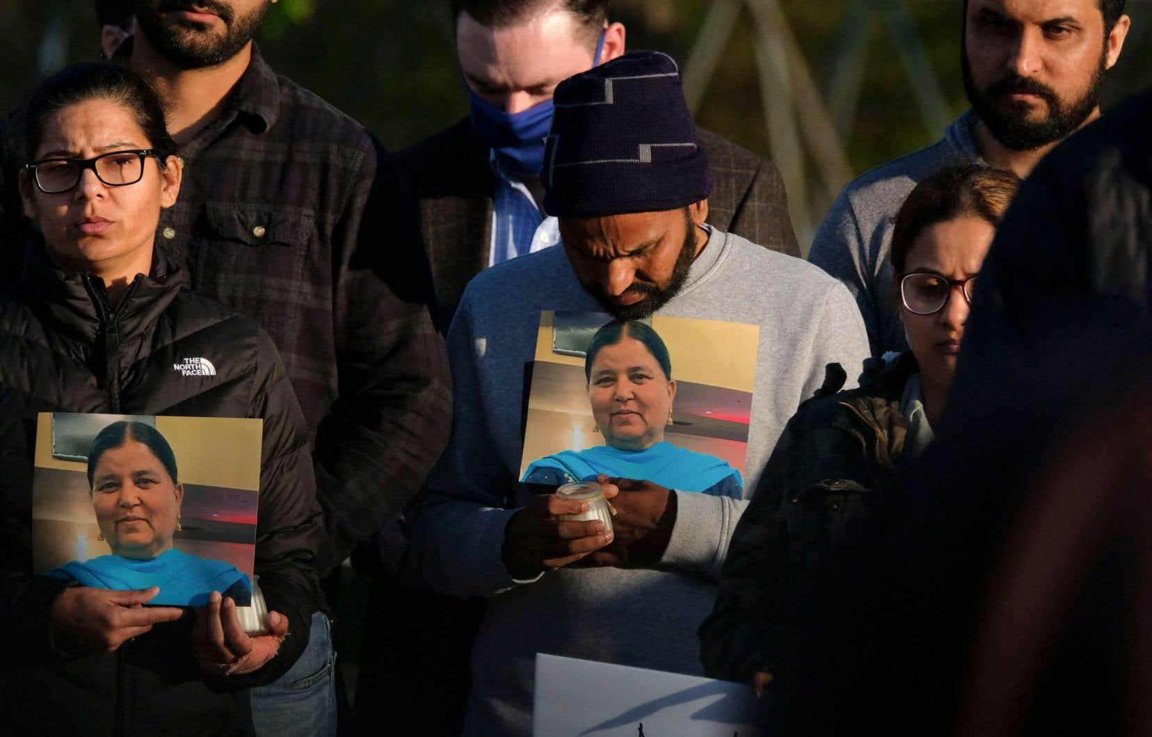 Des membres de la famille tiennent une photo de leur être cher lors d'une veillée aux chandelles à Krannert Park à Indianapolis, samedi soir dernier, en souvenir des victimes d'une fusillade de masse dans un établissement de la compagnie FedEx.