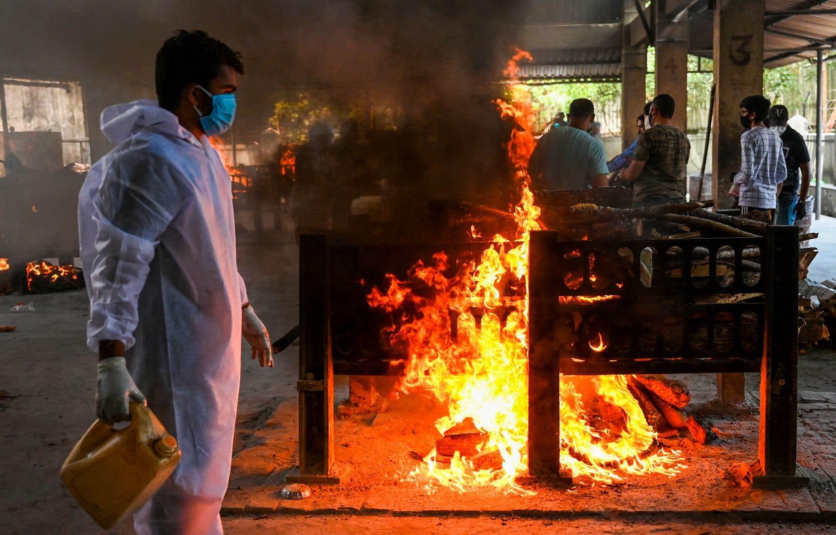 Un membre du personnel du crématorium brûle les restes d'une victime du coronavirus, décédée lors d'un incendie qui a tué 13 patients à l'hôpital Vijay Vallabh de Virar.