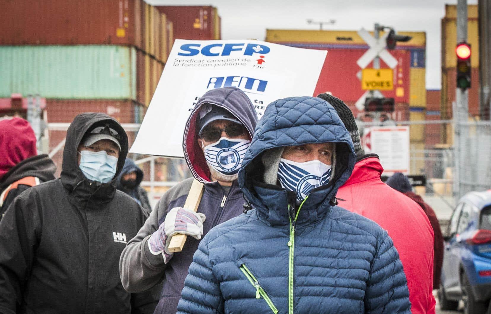 Des débardeurs en grève devant une entrée du port de Montréal