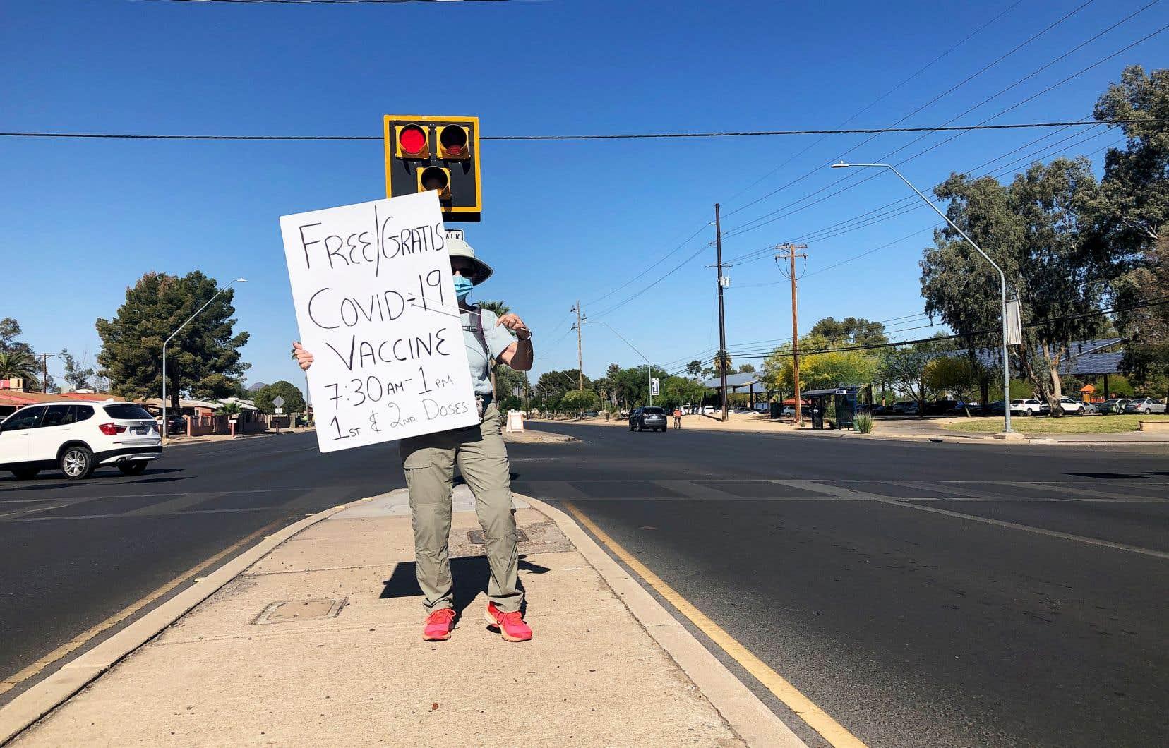 Au milieu d'un boulevard passant, Judy Winger, jeune retraitée, rabat bénévolement les voitures vers le site de vaccination à Tucson, en Arizona.