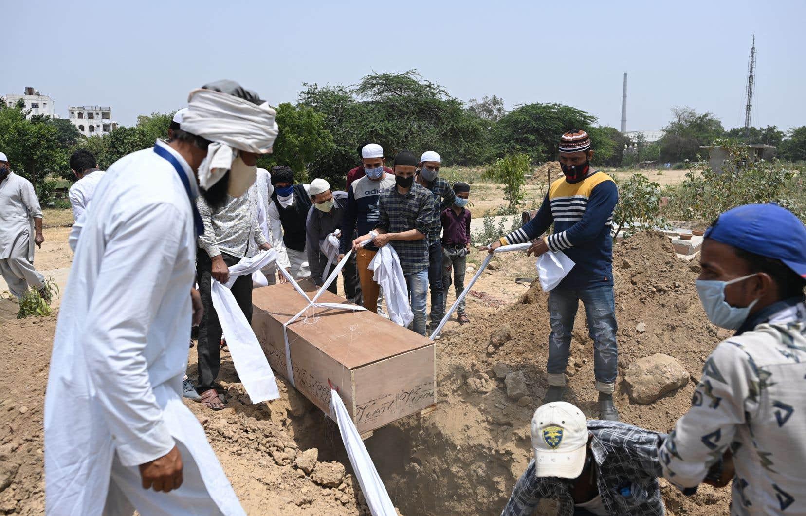 En Inde, ce sont 201 187 personnes qui ont succombé à l'épidémie, dont 3293 au cours des 24 dernièresheures, selon le ministère de la Santé. Sur la photo, le corps d'une victime est mis sous terre, mercredi, à New Delhi.