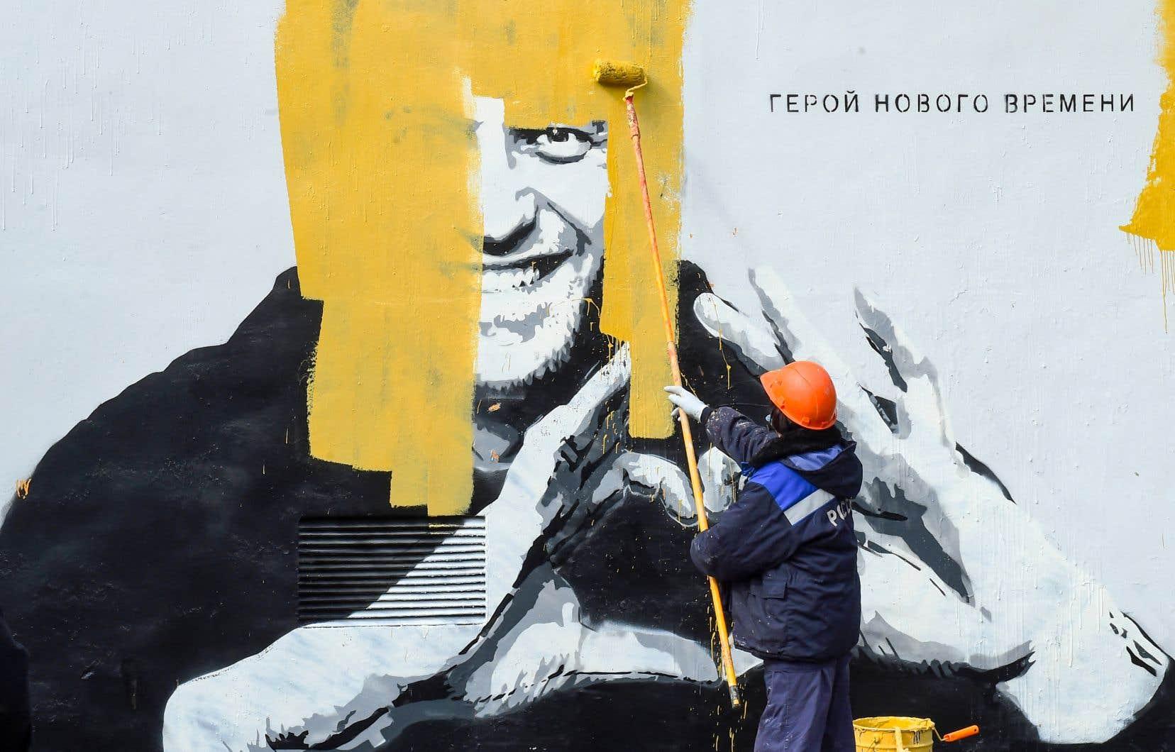 Un ouvrier recouvrait mercredi un graffiti représentant l'opposant russe Alexeï Navalny, accompagnéde l'inscription «Le héros des temps nouveaux», à Saint-Pétersbourg.