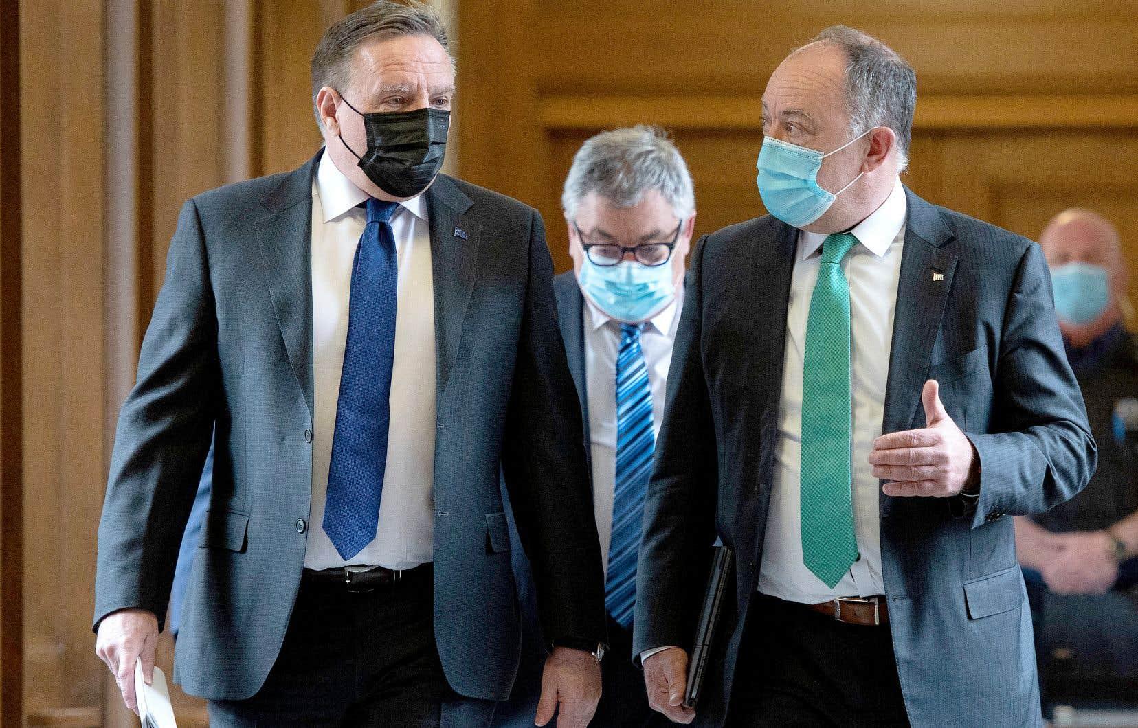 Le premier ministre, François Legault, le ministre de la Santé, Christian Dubé, et le directeur national de santé publique, Horacio Arruda, (à l'arrière) se rendant au point de presse sur la situation sanitaire, mardi.
