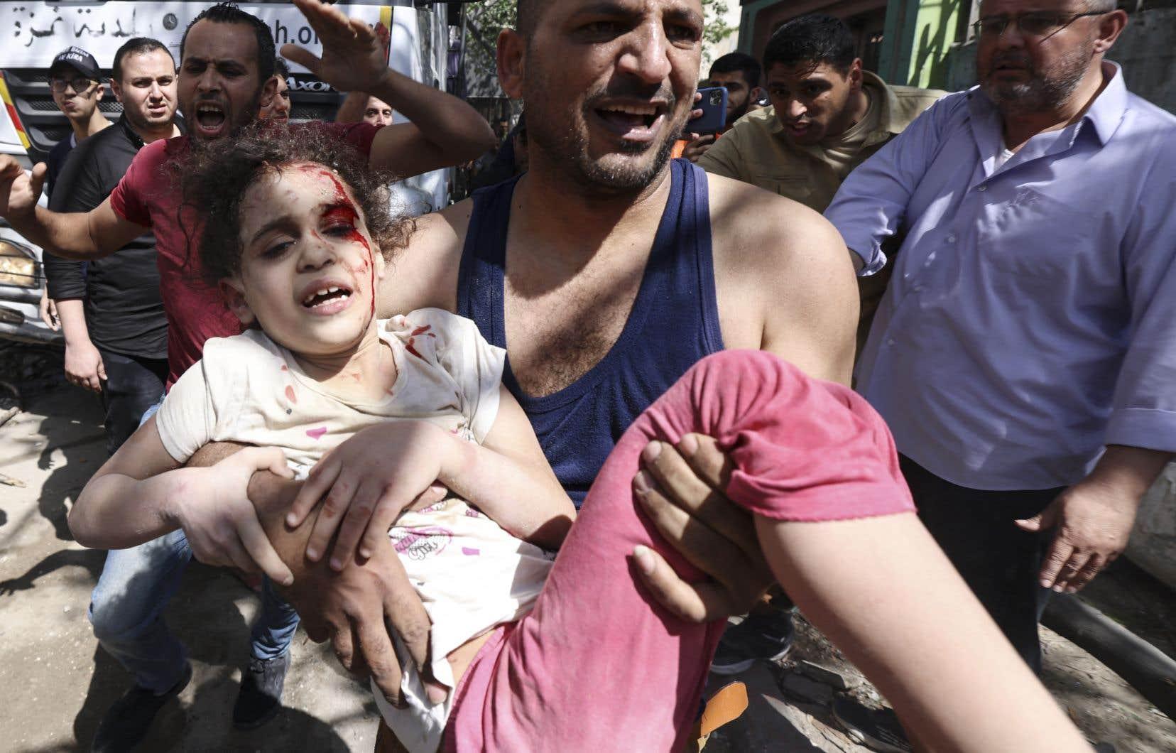 Un jeune Palestinienne blessée était évacuée dimanche après des frappes israéliennes dans le quartier résidentiel de Rimal, à Gaza.