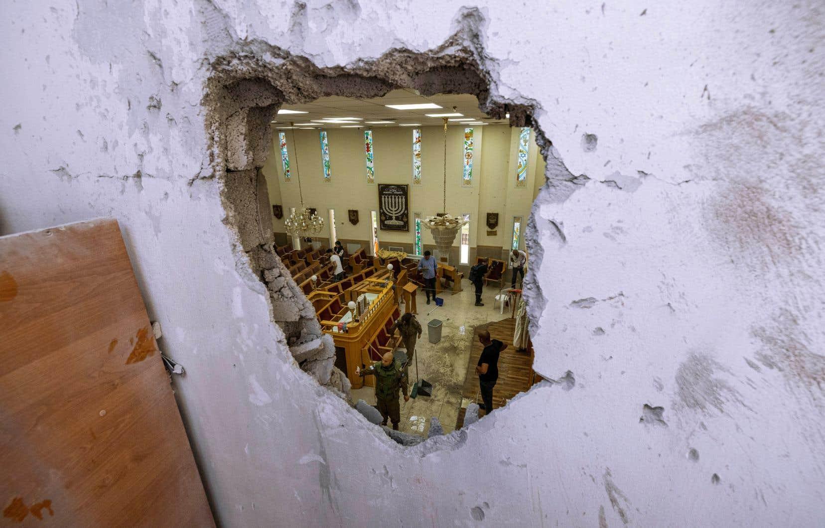 Les forces de sécurité israéliennes inspectent une synagogue endommagée par une roquette tirée depuis la bande de Gaza, à Ashkelon, le 16 mai 2021.