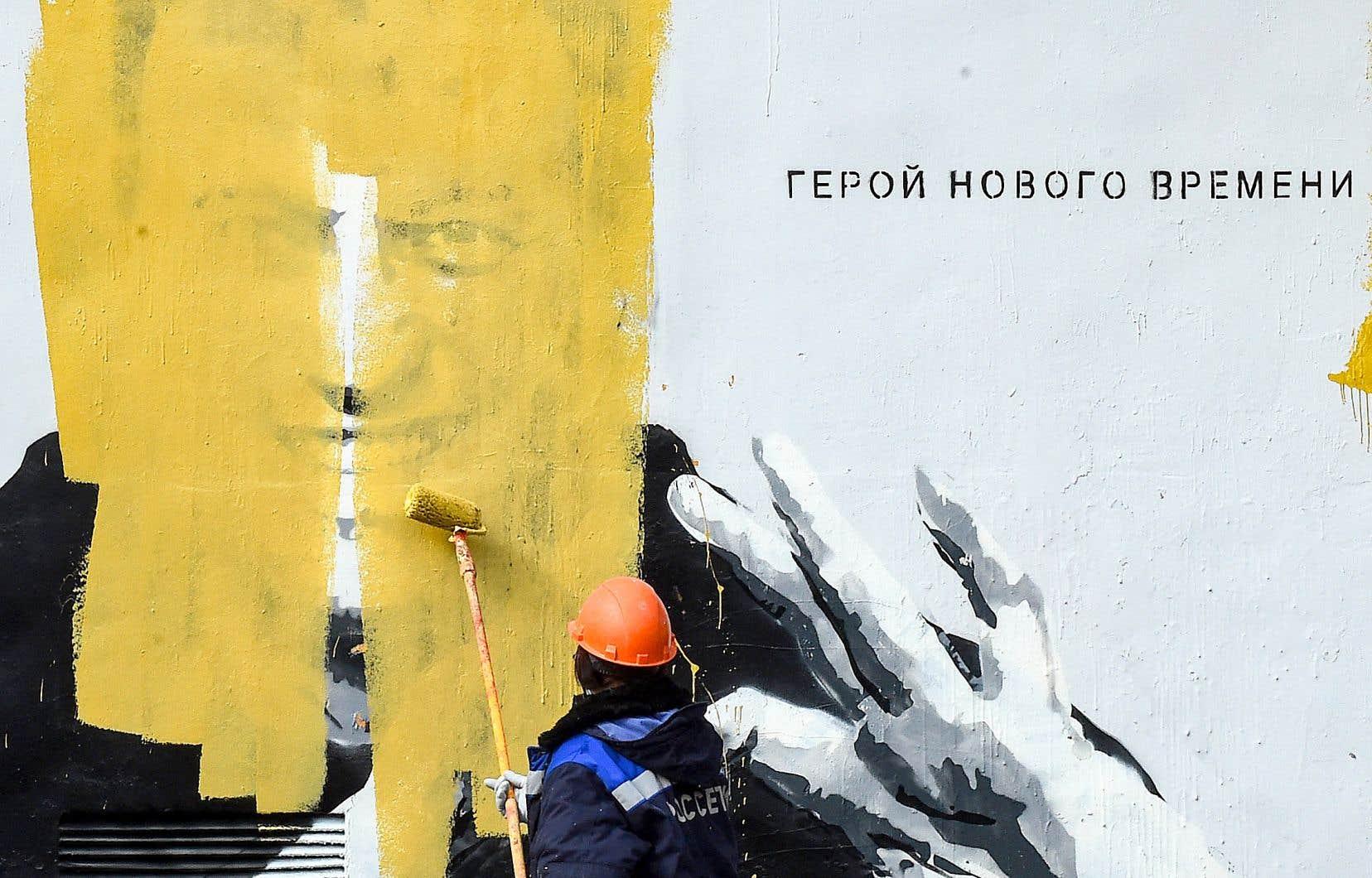 Un ouvrier recouvre une murale représentant l'opposant russe Alexeï Navalny, accompagnée de l'inscription «Le héros des temps nouveaux», à Saint-Pétersbourg.