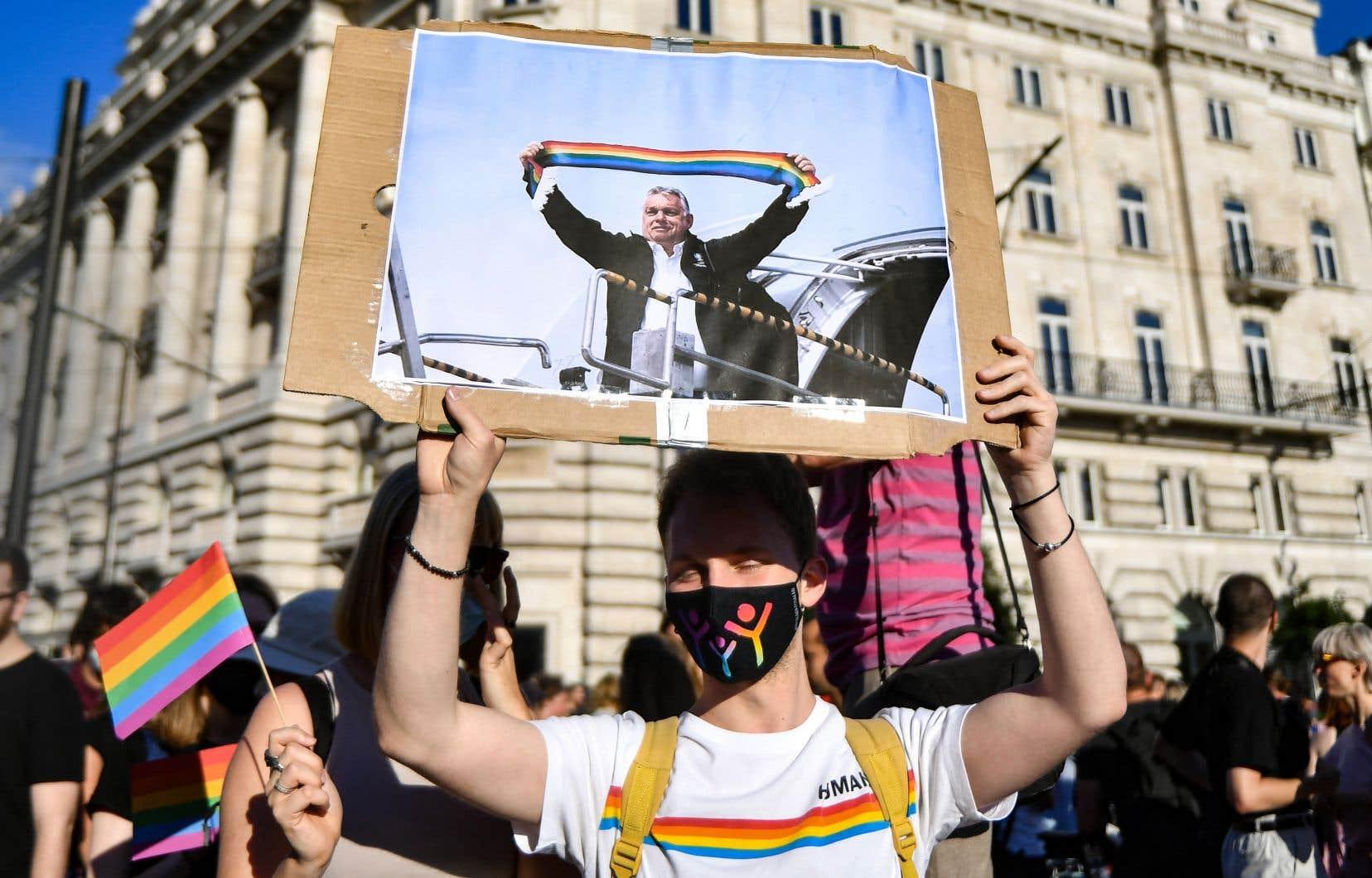 Des milliers de personnes étaient descendues lundi soir dans les rues de Budapest pour fustiger les «cruelles campagnes politiques» du pouvoir. Sur notre photo, un manifestant parmi la foule brandissait une pancarte montrant le premier ministre, Viktor Orbán, une écharpe aux couleurs de l'arc-en-ciel à la main.
