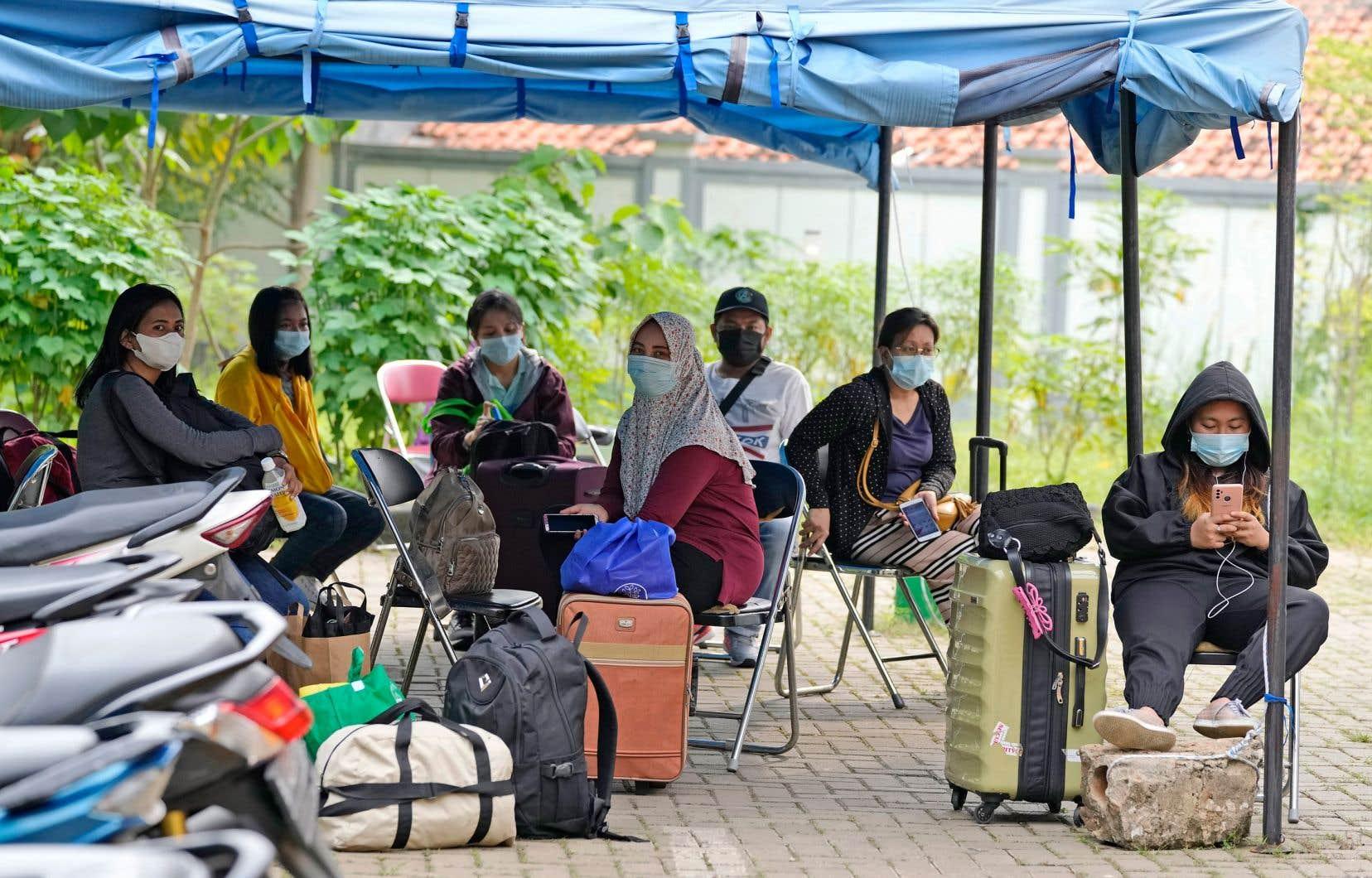 Des personnes déclarées positives attendaient vendredi d'être transférées à un hôpital de Jakarta, en Indonésie. Le pays a connu des pics de nouveaux cas récemment, attribués aux déplacements durant la fête Eid al-Fitr et à l'arrivée de variants.