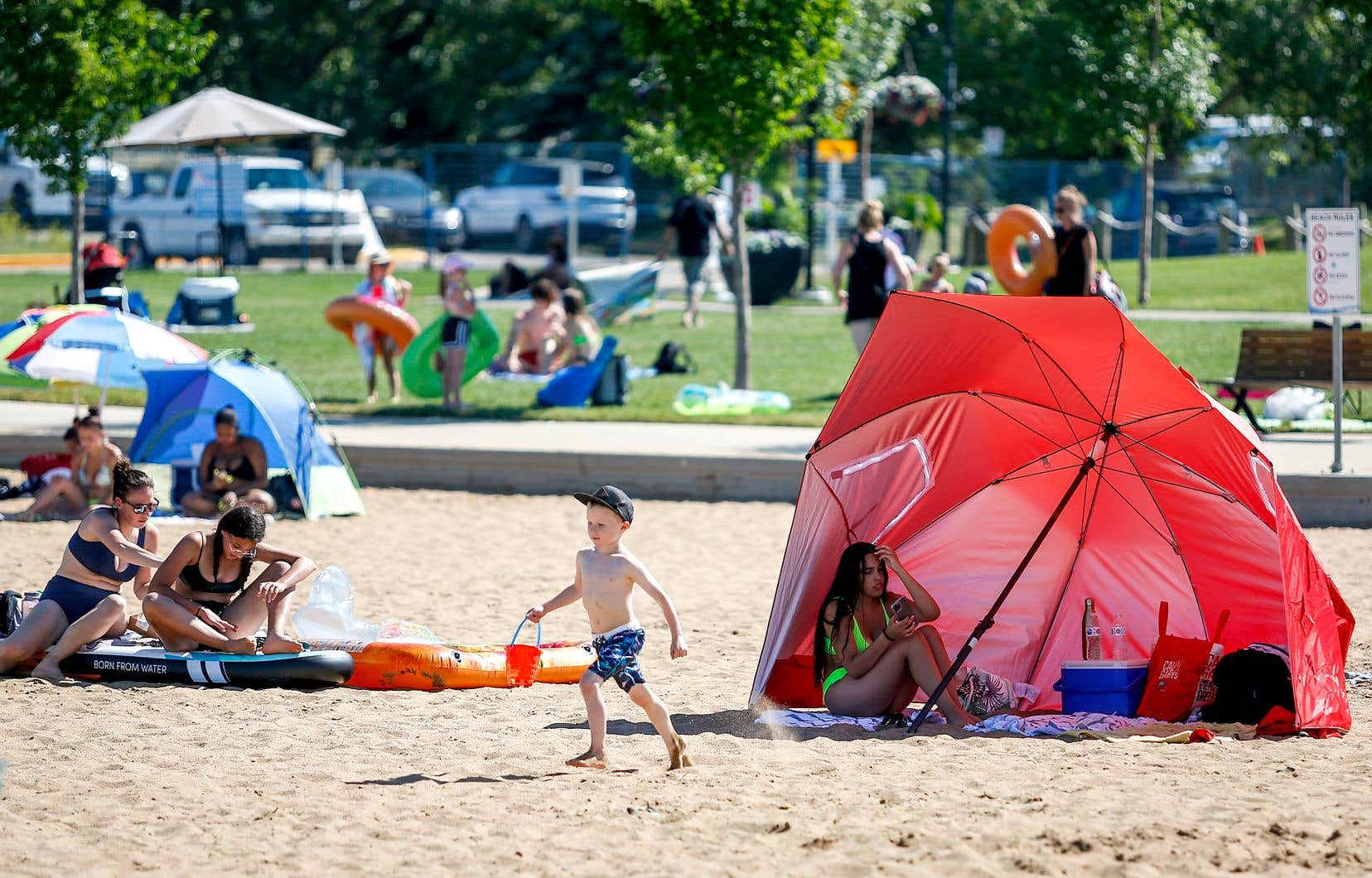 Des résidents de Chestermere, en Alberta, tentent d'échapper à la chaleur sur une plage, mardi.