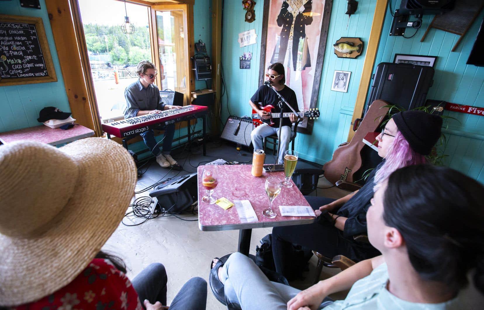 Une poignée de festivaliers se sont réunis pour une heure de musique avec l'auteur-compositeur-interprète Gab Bouchard (à droite) au bar Le Gibard, mardi, lors du Festival de la chanson de Tadoussac.
