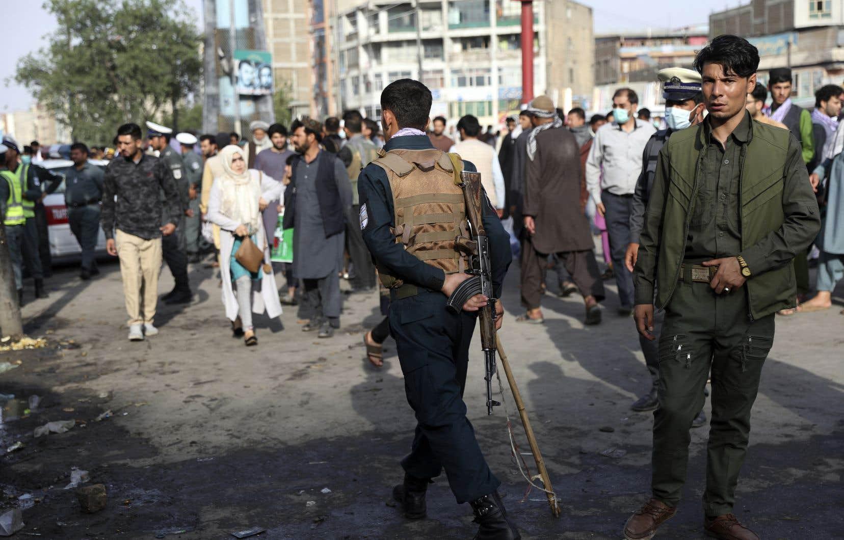 Un agent des forces de sécurité afghanes inspecte le site de l'explosion d'une bombe à Kaboul, le mardi 13 juillet. Les talibans ont appelé les citadins afghans à se rendre pour éviter les combats dans les villes.