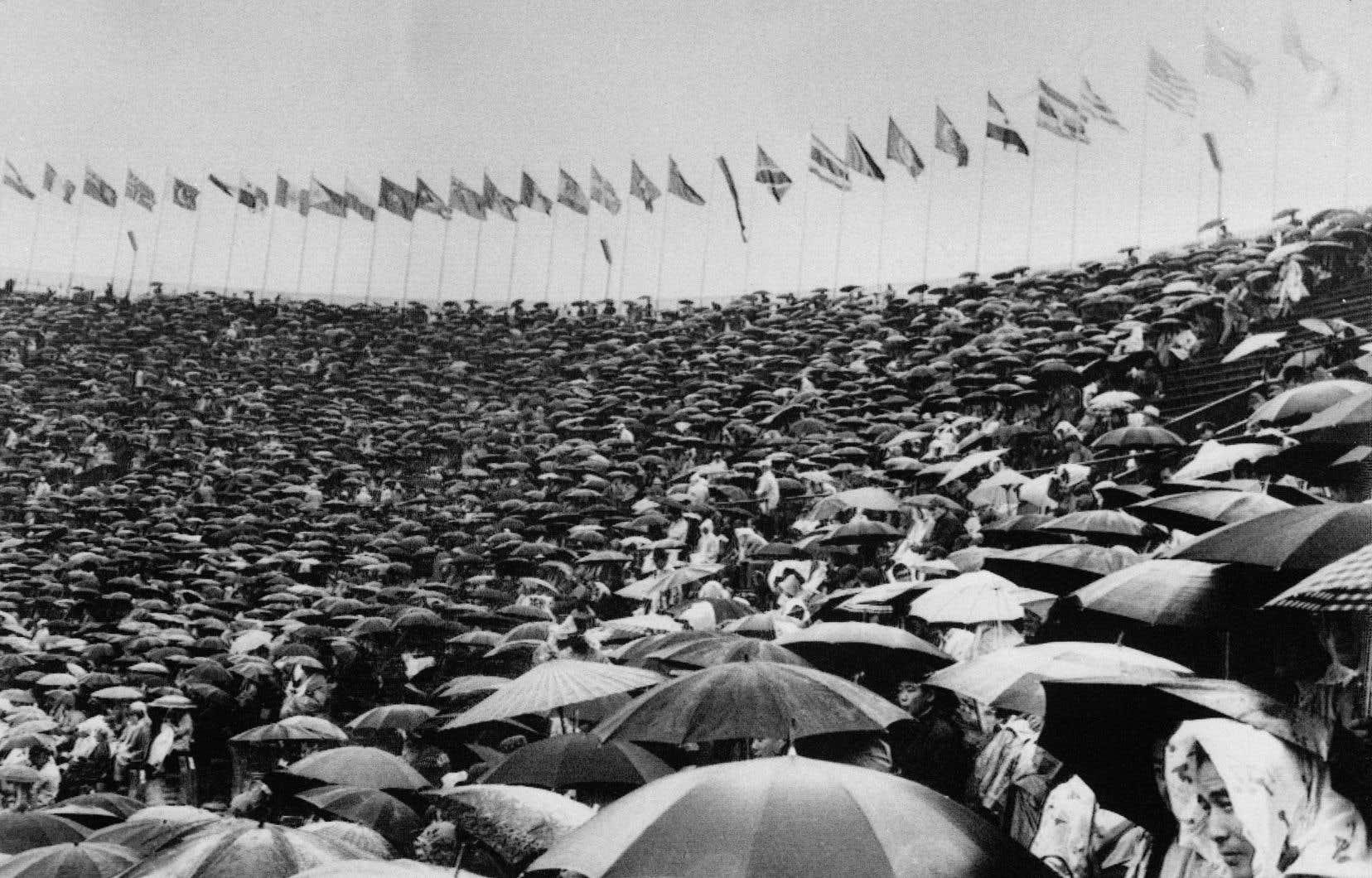 Des spectateurs massés dans l'ancien Stade olympique national, à Tokyo, le 14 octobre 1964, sous une forte pluie
