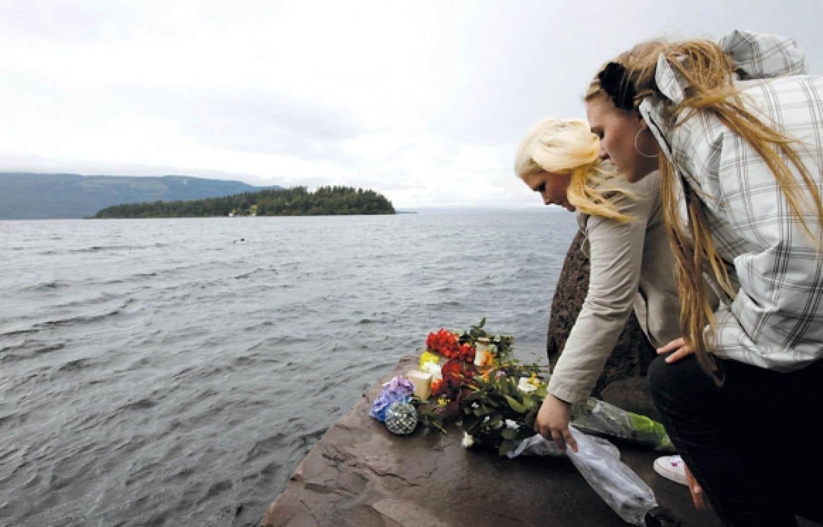 Des jeunes filles ont déposé des fleurs hier en face de l'île Utoeya, où un tireur déguisé en policier a ouvert le feu vendredi sur les participants de l'université d'été du Parti travailliste norvégien.