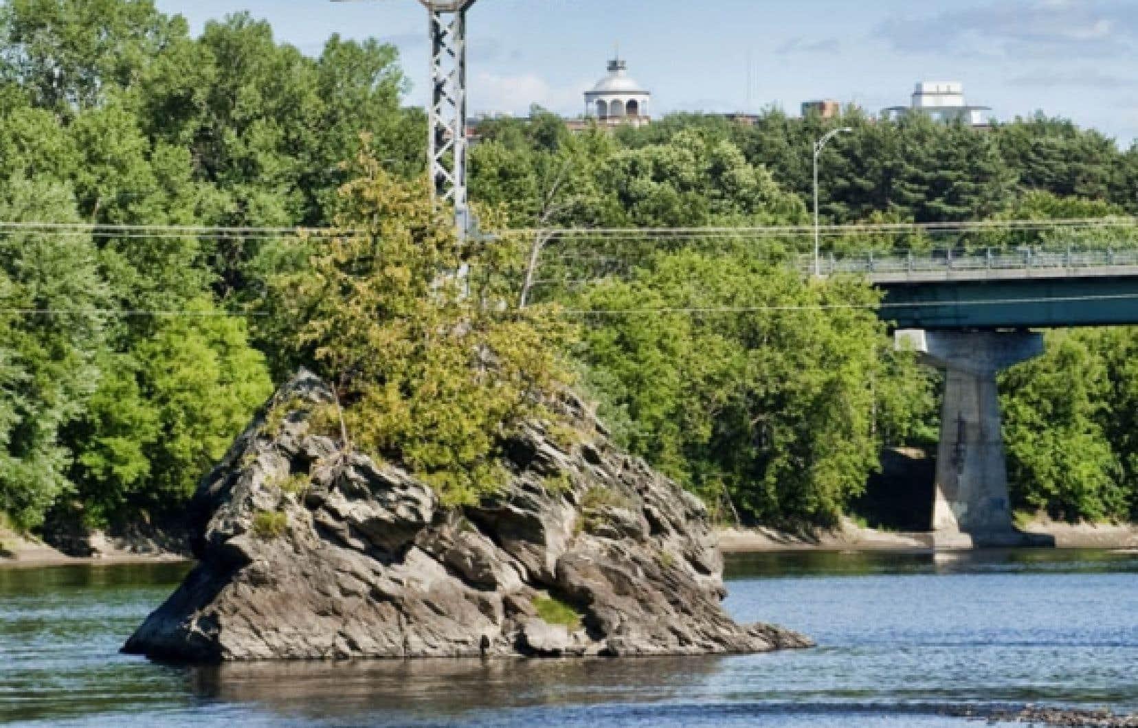 Le Rocher du Pin Solitaire, maintenant appelé Mena'sen, au milieu de la rivière Saint-François, au cœur de la ville de Sherbrooke.<br />