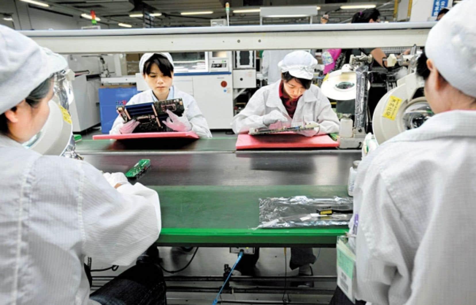 Des ouvriers d'une usine de Foxconn, à Shenzhen, en Chine. Géant mondial de la sous-traitance en électronique, pour Apple notamment, Foxconn veut automatiser davantage sa production en installant 300 000 machines sur les chaînes en 2012 et 1 million en trois ans pour remplacer 500 000 employés.<br />