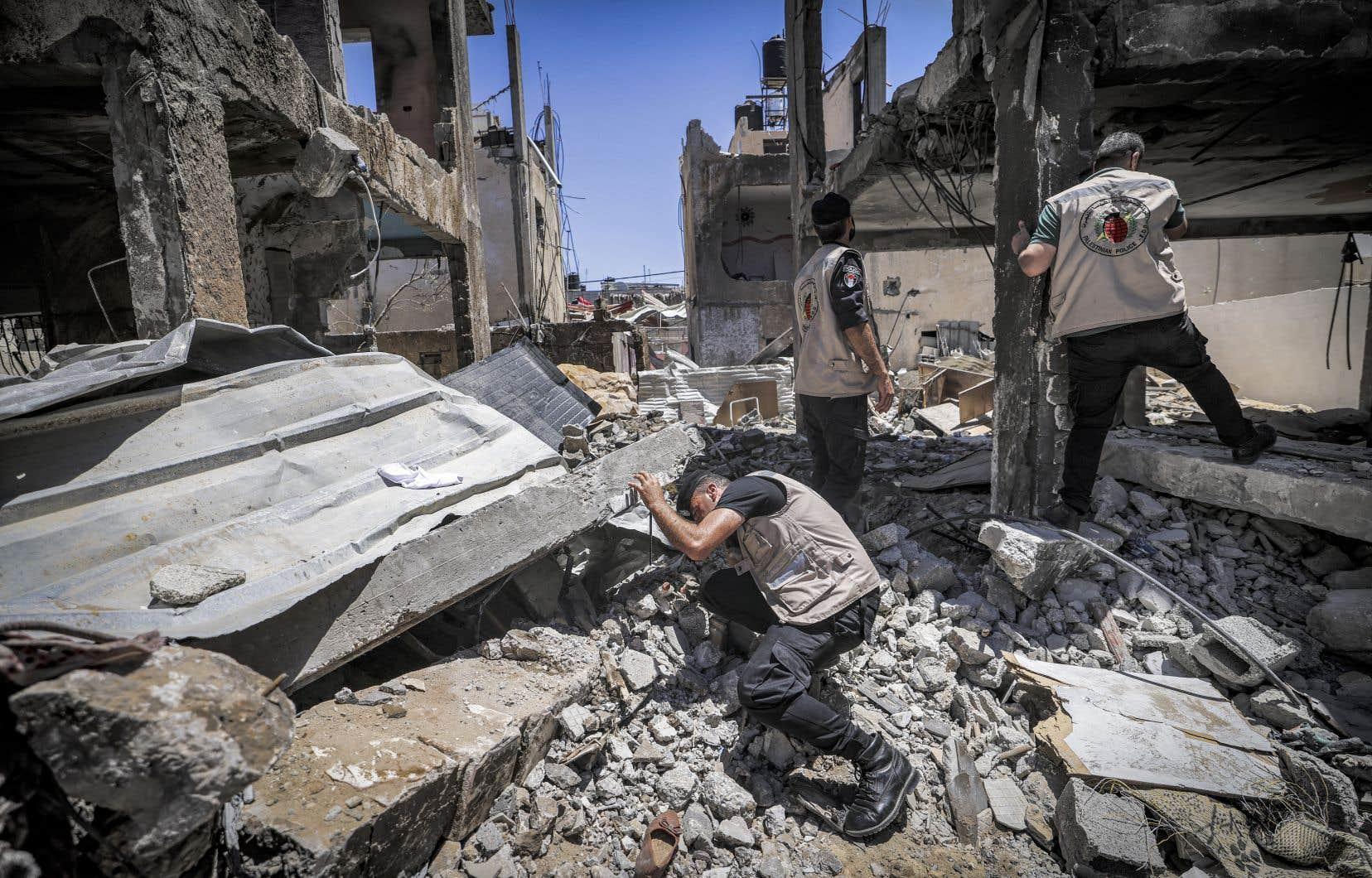 Des experts en explosifs fouillent un bâtiment détruit à la recherche de projectiles non explosés à la suite du conflit de mai 2021 avec Israël, dans la ville de Gaza.