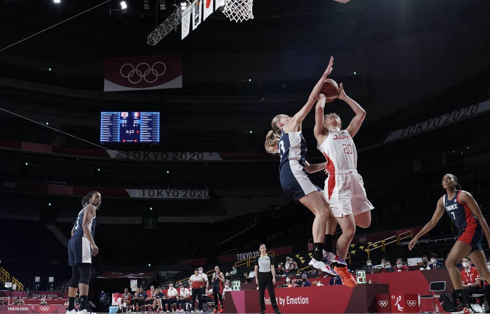 L'arbitre internationale Mariepier Malo (qui porte le chandail gris et noir sur la photo) était l'arbitre en chef mardi lors du match de basketball féminin opposant la France au Japon. Il s'agissait de son premier match aux Jeux.