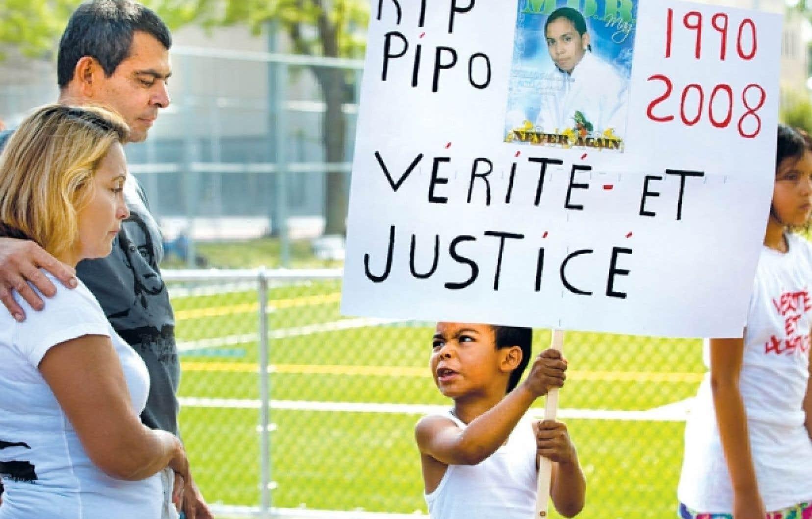 Un jeune garçon en colère, brandissant une pancarte, regarde les parents de Fredy Villanueva. Environ 75 personnes se sont jointes à la famille Villanueva pour marcher à la mémoire du jeune homme décédé le 9 août 2008.<br />