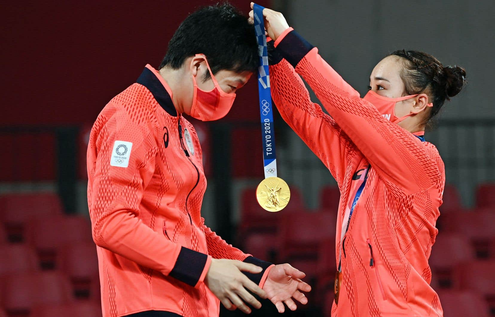 Le Japonais Jun Mizutani reçoit la médaille d'or de sa coéquipère Mima Ito au haut du podium de tennis de table à Tokyo, lundi.
