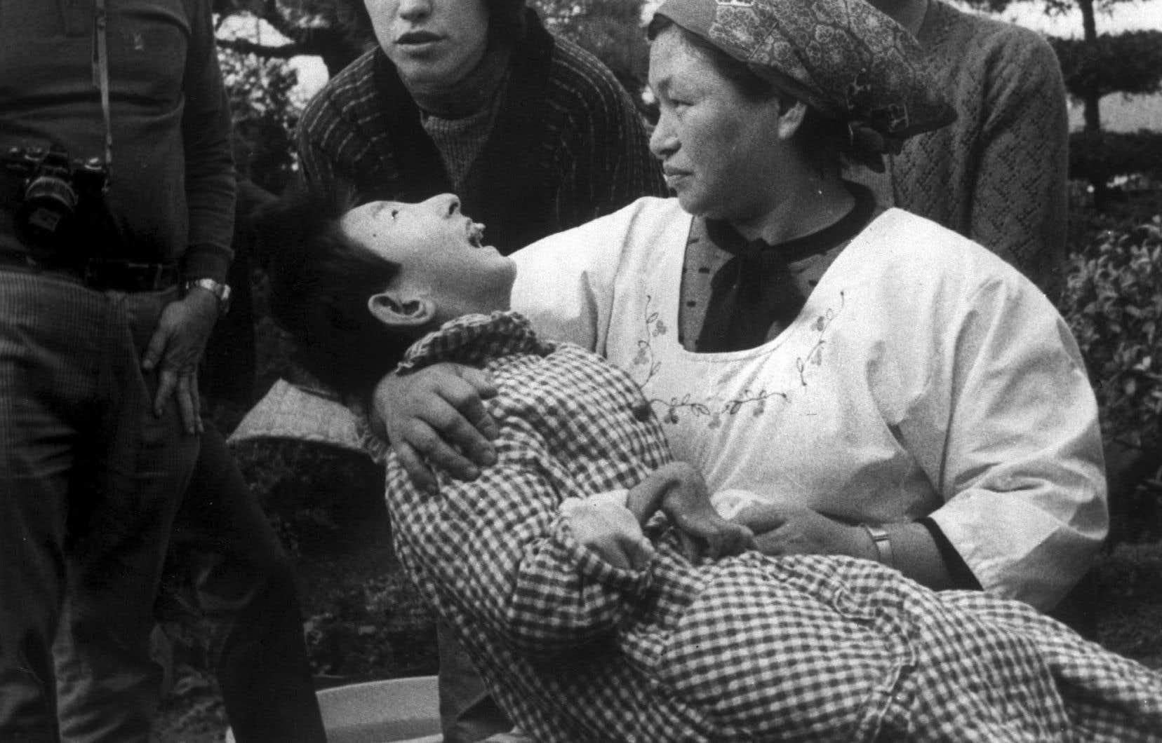 En 1973, une femme tient dans ses bras une victime de la contamination chimique à Minamata qui a une malformation de la main.