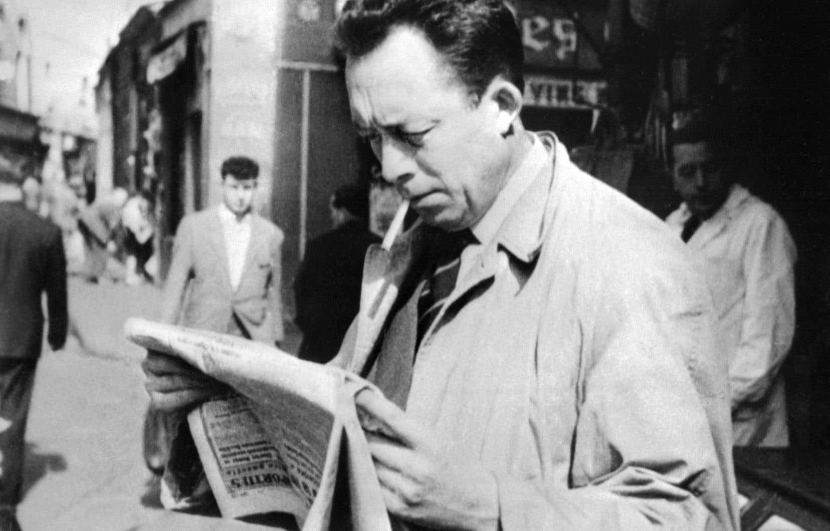 L'écrivain français, journaliste, philosophe et Prix Nobel de littérature en 1957, Albert Camus, lisant un journal, cigarette aux lèvres, à Paris en 1953.