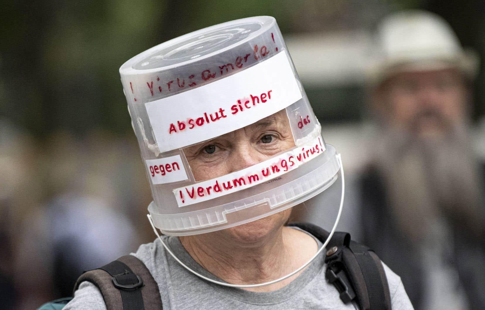 Un manifestant arborerant un seau en plastique avec l'inscription «Absolument en sécurité contre le virus de la stupidité»