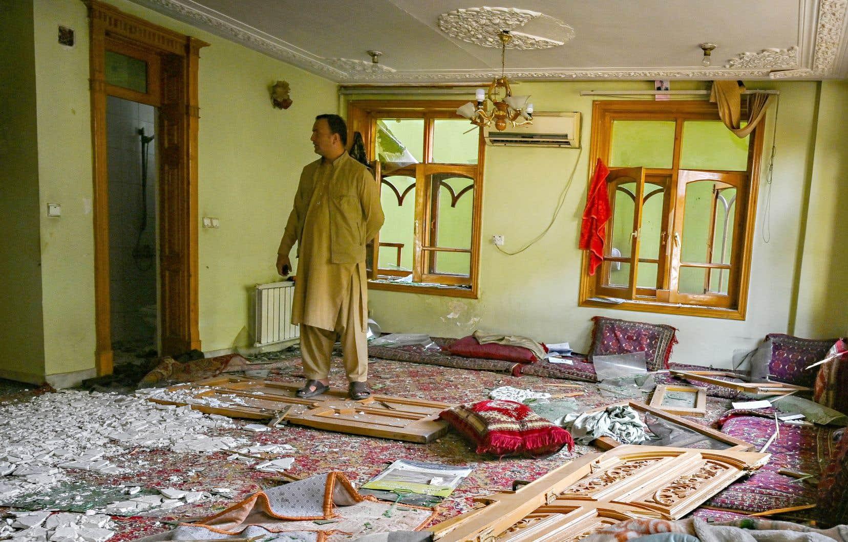Un homme constatait mercredi les dommages causés à un édifice, au lendemain de deux grosses explosions à Kaboul.