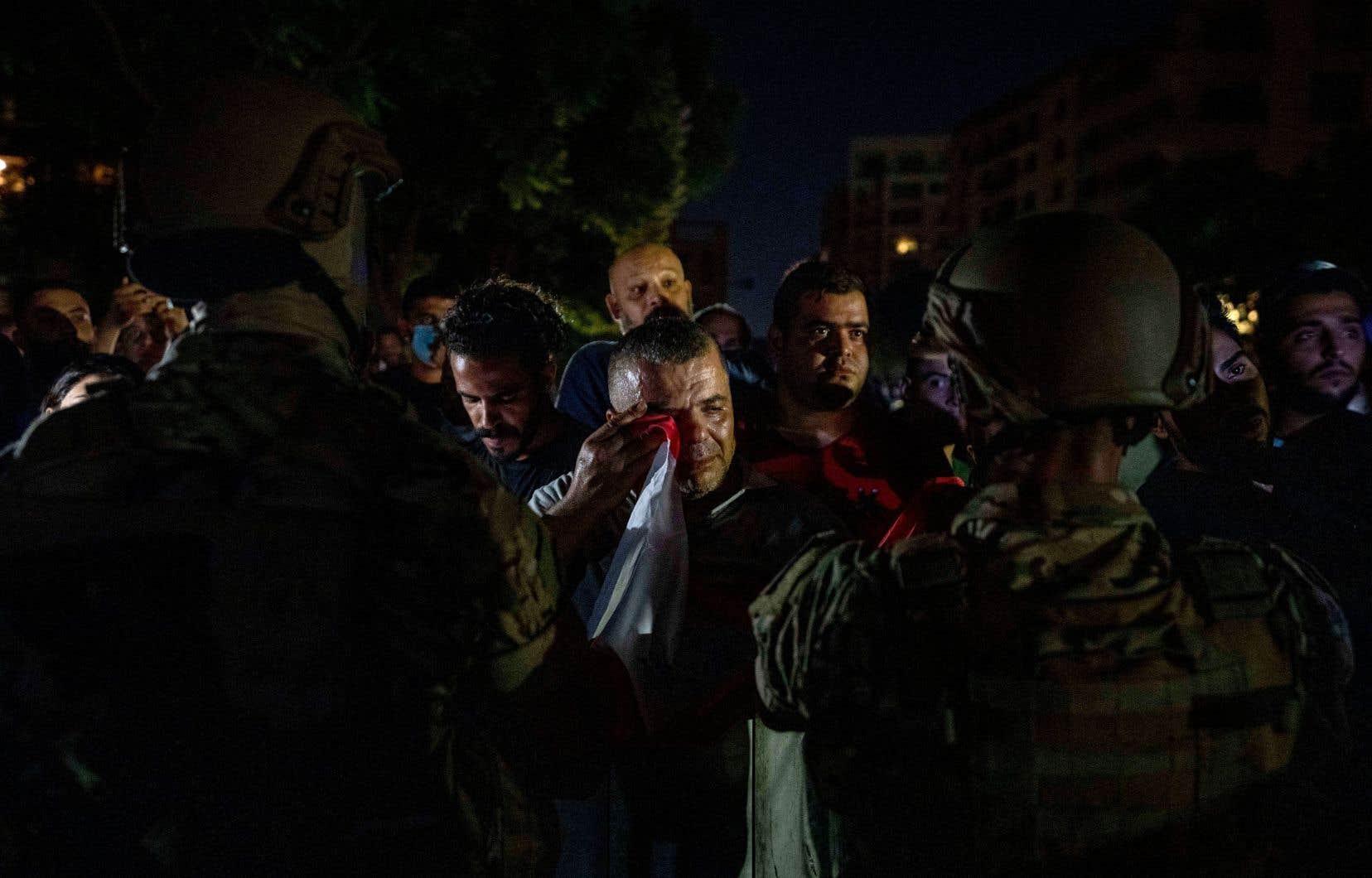 Un manifestant antigouvernemental utilise le drapeau national libanais pour essuyer ses larmes lors d'une manifestation devant la résidence du premier ministre libanais désigné Najib Mikati à Beyrouth. Des manifestants se sont rassemblés dans les rues de Beyrouth un jour après le meurtre de 28 personnes en raison d'une explosion d'entrepôt où le carburant était illégalement stocké.