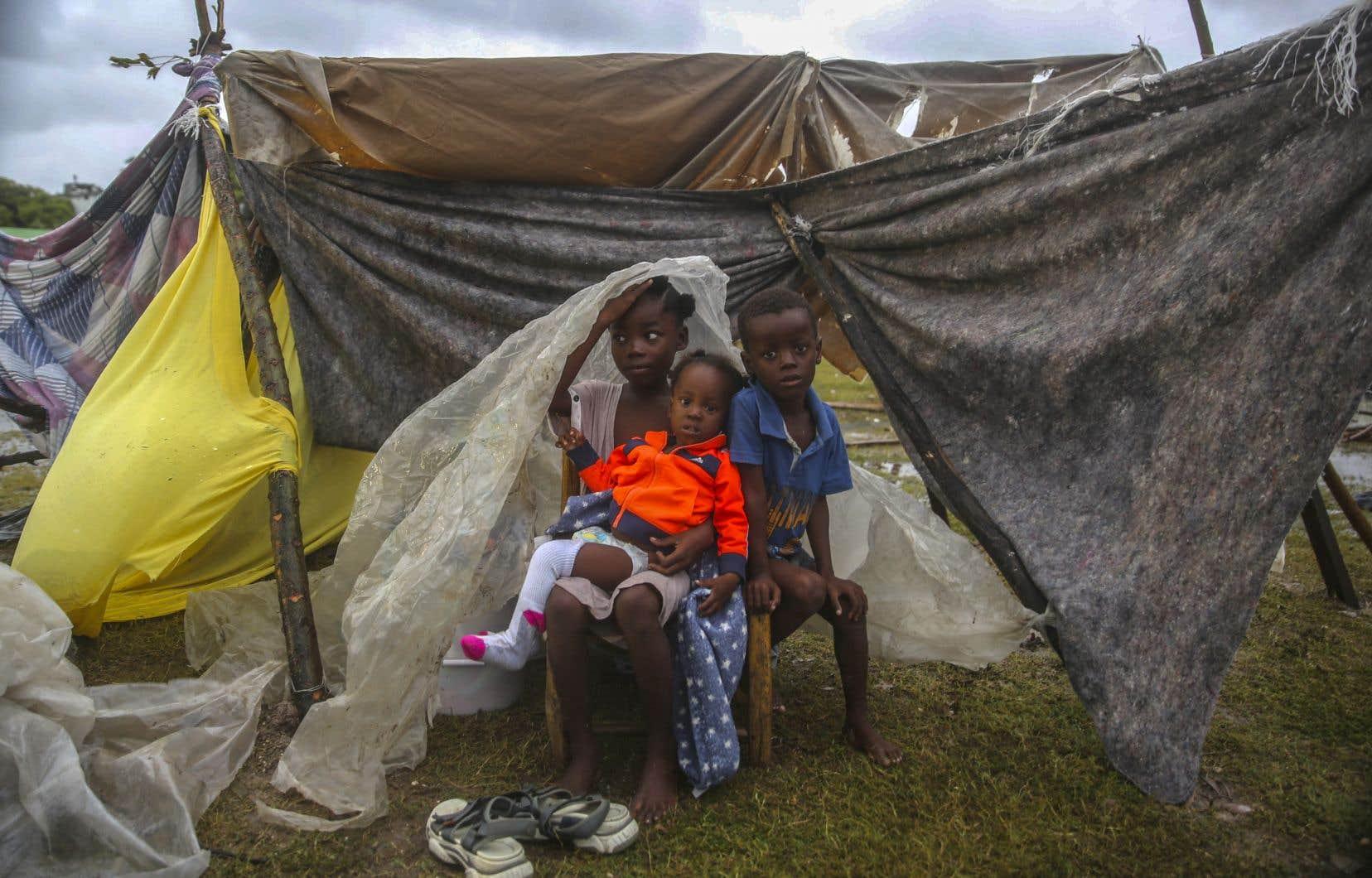 Des enfants déplacés par le séisme se blottissent sous un morceau de plastique le matin après que la tempête tropicale Grace a balayé Les Cayes, en Haïti, mardi le 17 août 2021, trois jours après un séisme de magnitude 7,2.