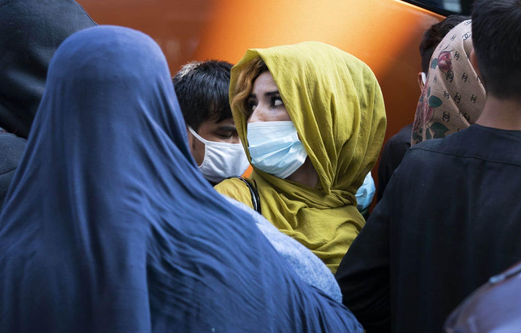 Le Canada avait rapatrié plus de 2700 personnes, en date de mercredi, dont 1000 Afghans. Des centaines d'autres demeurent cependant sur le terrain, incapables d'accéder à l'aéroport de Kaboul ou de monter à bord des vols canadiens. Sur la photo, une famille d'Afghans à l'aéroport international de Washington-Dulles, mercredi.