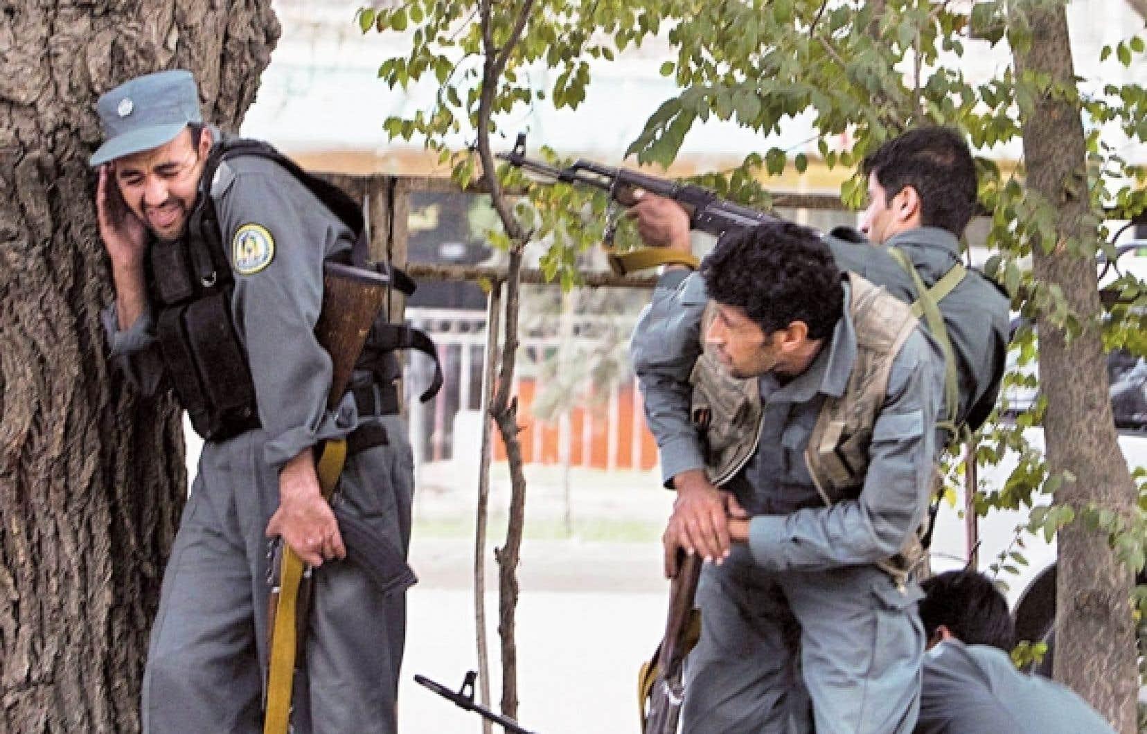 Des policiers afghans ripostent aux tirs nourris des insurg&eacute;s dans le quartier fortifi&eacute; des ambassades, au centre de la capitale afghane.<br />