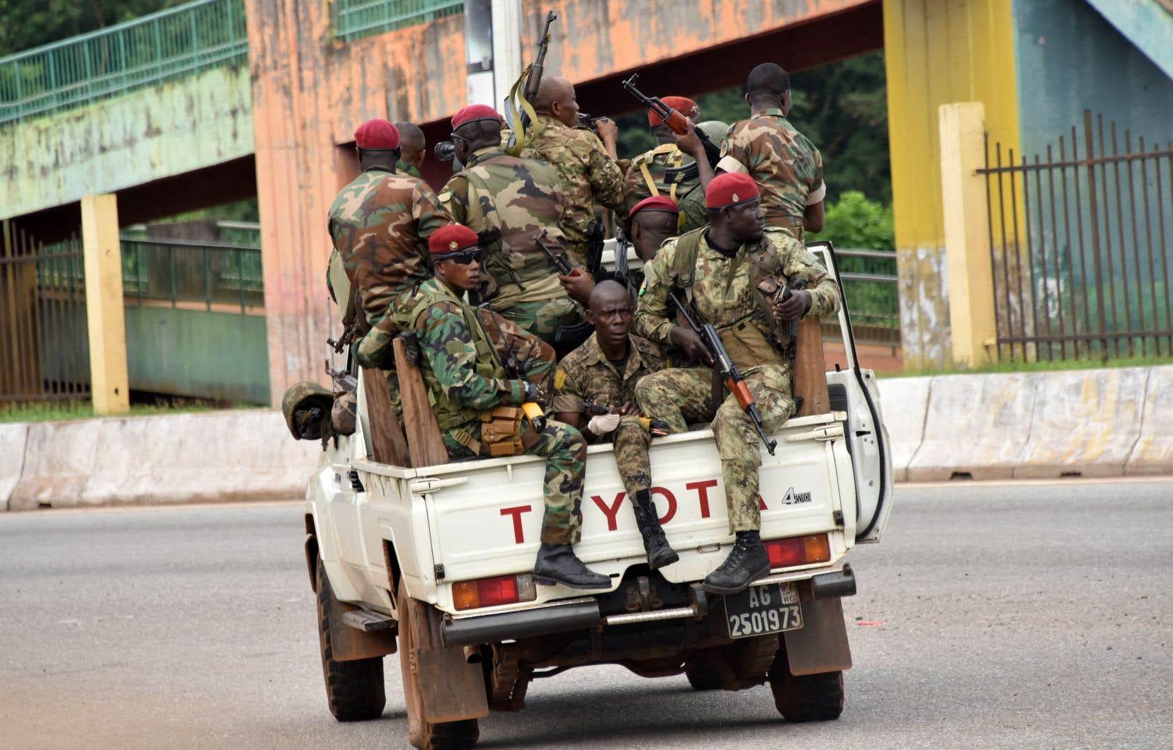 Des membres des Forces armées guinéennes traversent le quartier central de Kaloum à Conakry le 5 septembre 2021 après que des coups de feu aient été entendus.