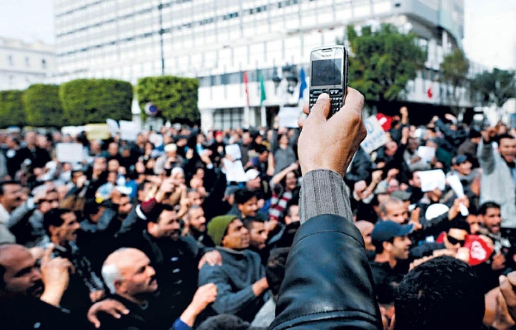 Un manifestant tunisien photographiait la foule lors d'un rassemblement à Tunis, plus tôt cette année.<br />