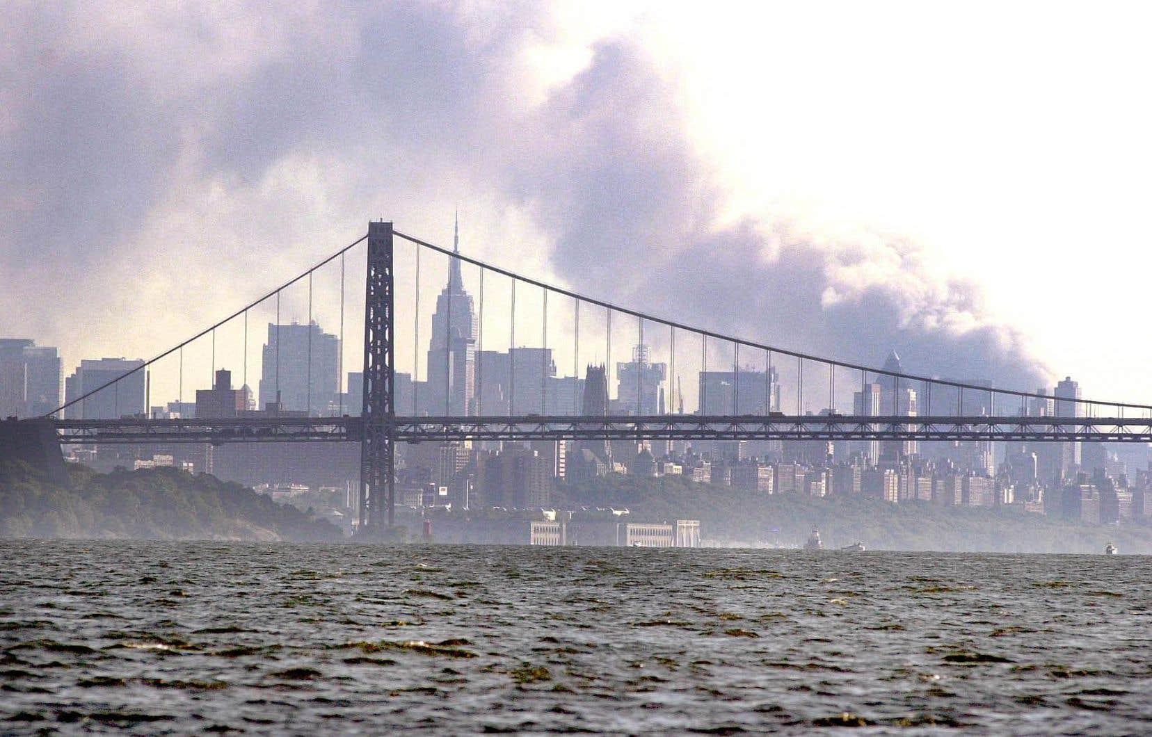 De la fumée s'échappe de l'horizon de New York le 11 septembre 2001 après que deux avions détournés se soient écrasés sur le World Trade Center.