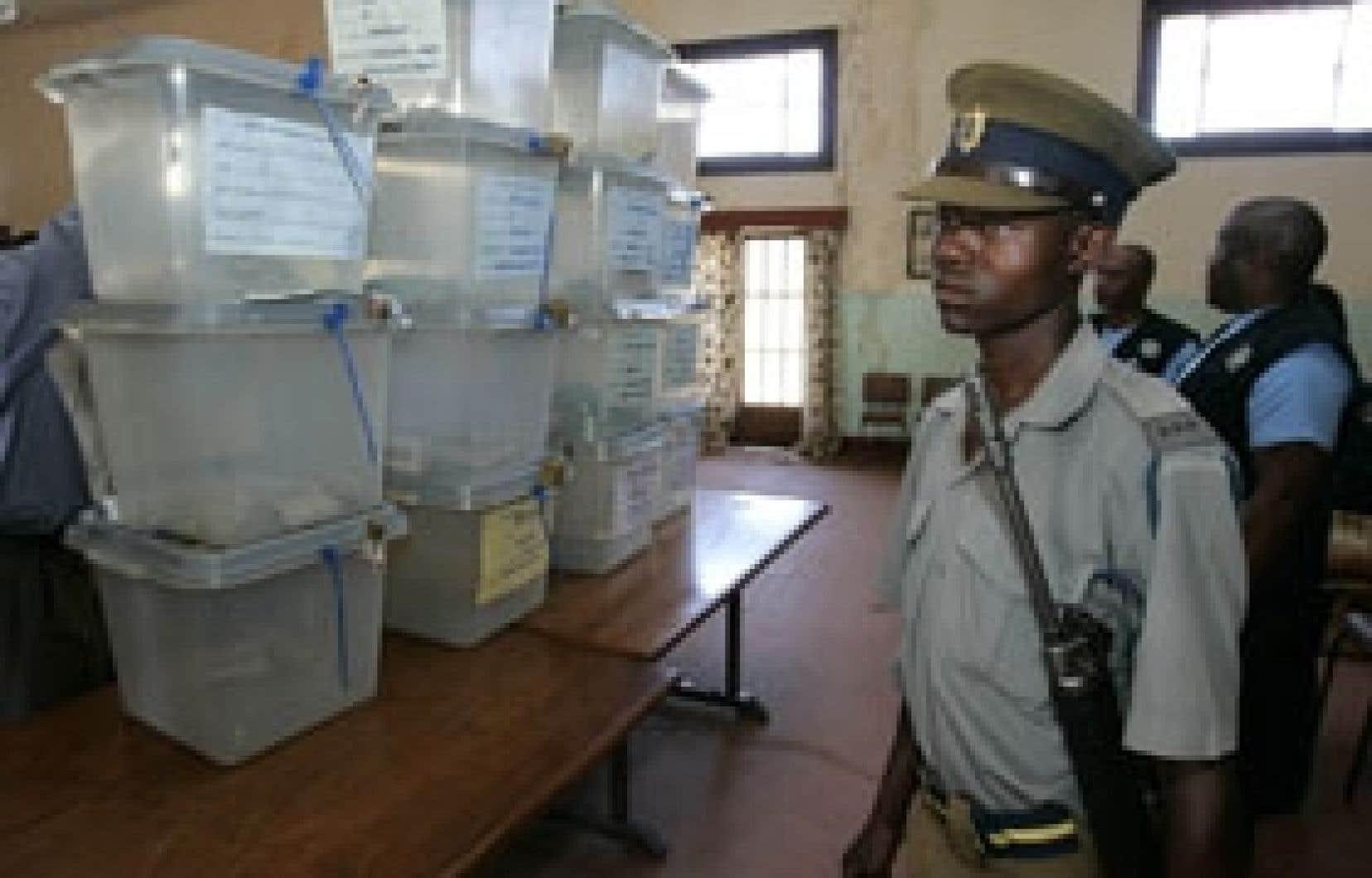 Un policier surveillait dimanche des urnes à Harare.