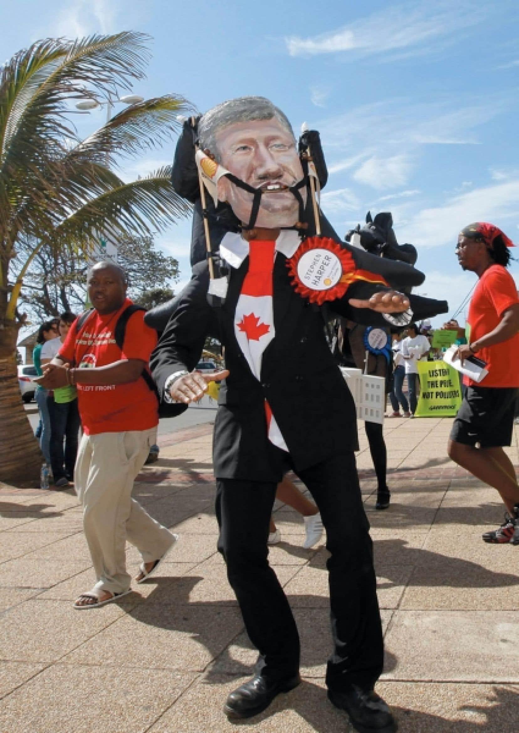 Un manifestant portant un masque &agrave; l&rsquo;effigie du premier ministre Harper d&eacute;nonce la position du Canada face au Protocole de Kyoto, &agrave; l&rsquo;occasion&nbsp; de la conf&eacute;rence de Durban sur les changements climatiques, en d&eacute;cembre dernier.<br />