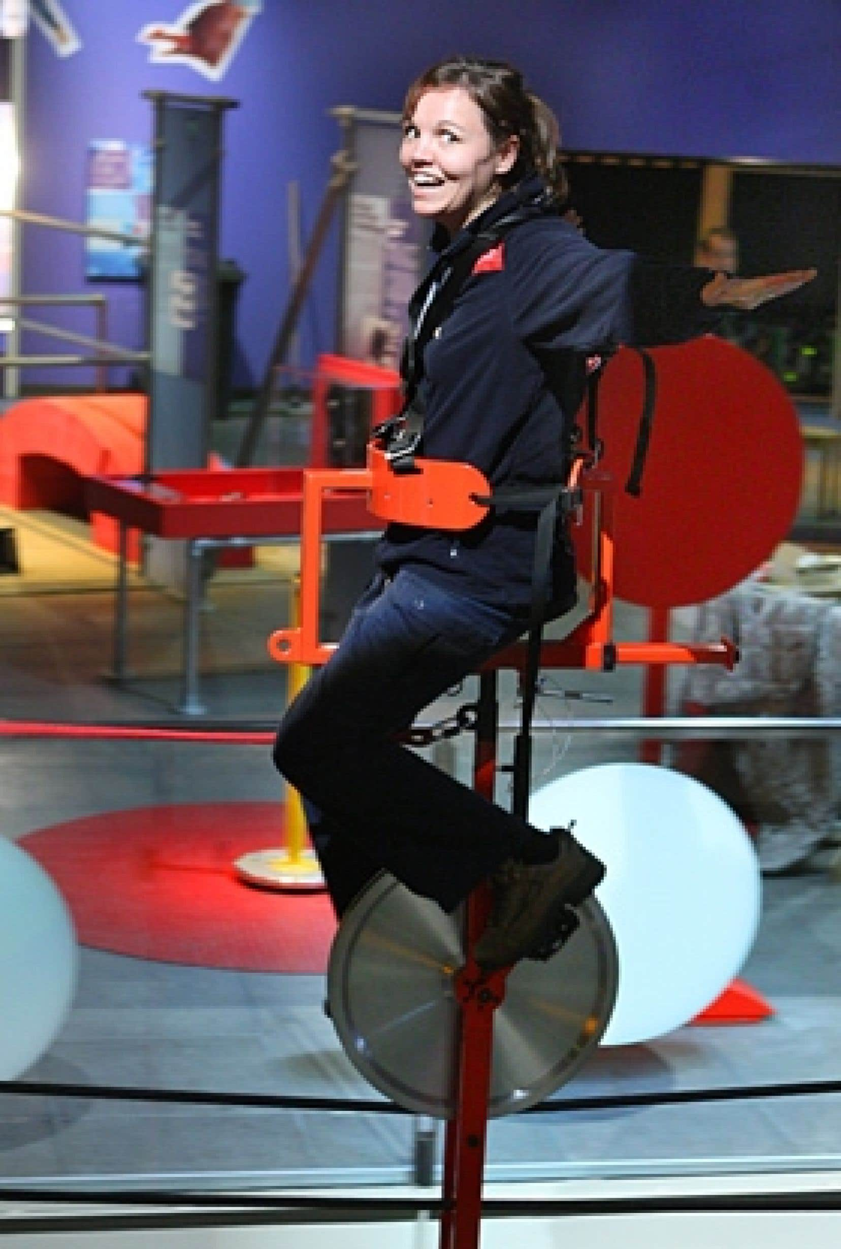June, une animatrice du Centre des sciences de Montréal, roule en équilibre sur un fil de fer tendu à sept mètres du sol, grâce à un poids de 200 kilos situé sous le monocycle.