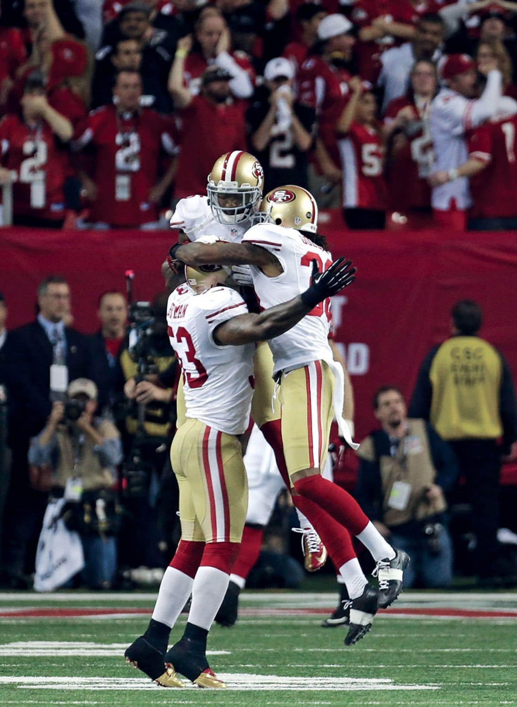 NaVorro Bowman, Darcel McBath et LaMichael James des 49ers célèbrent leur victoire contre les Falcons d'Atlanta 28-24 en finale de la Nationale, dimanche.