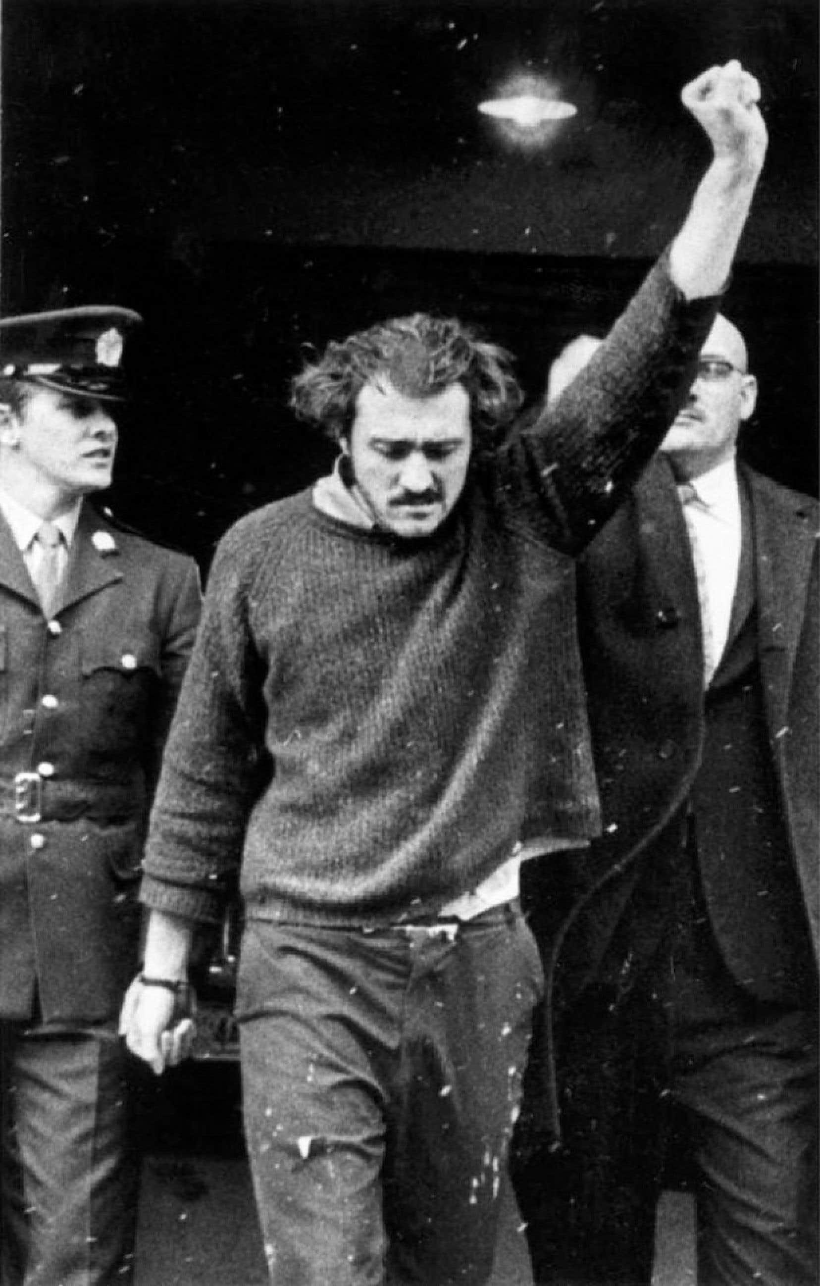 Paul Rose à l'entrée du palais de justice de Montréal en janvier 1971. Son garde-chiourme, AlbertLysachek (àdroite),s'empresserade rabaisser son poing combatif tendu vers le ciel.